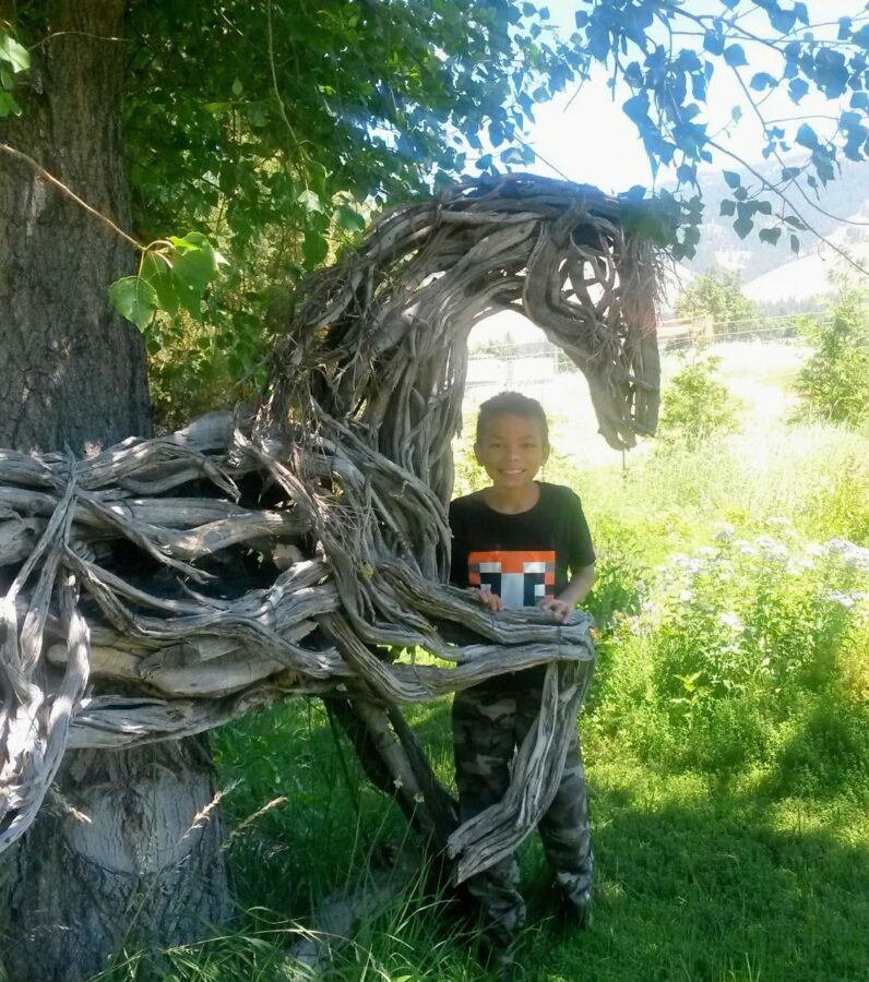 Photo of child with mixed media horse sculpture by Brenna Kimbro